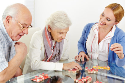 two elderly playing board games with their caregiver