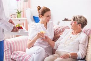 caregiver giving medicines to patient
